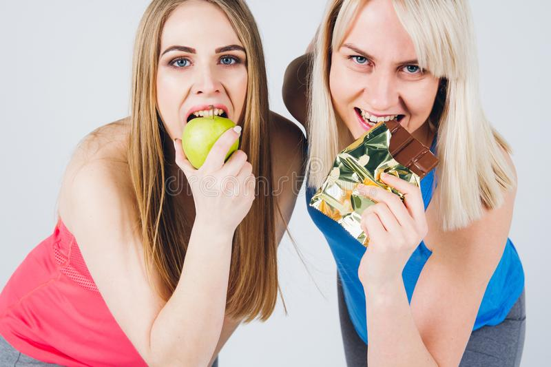 Pregnant girl and her friend eat an Apple and chocolate royalty free stock image