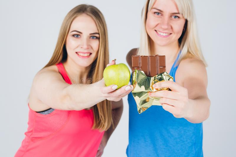 Pregnant girl and her friend eat an Apple and chocolate stock photos