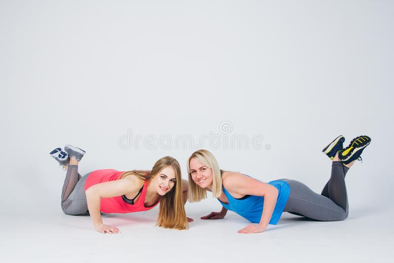 Pregnant girl and her friend are engaged in fitness stock photos