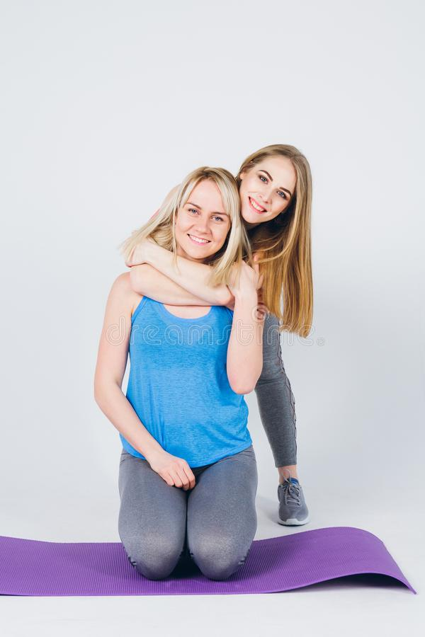 Pregnant girl and her friend are engaged in fitness stock photo