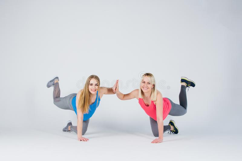 Pregnant girl and her friend are engaged in fitness stock images