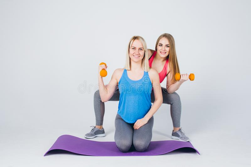 Pregnant girl and her friend are engaged in fitness royalty free stock photos