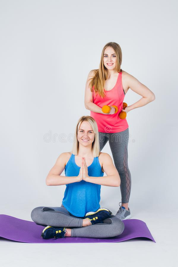 Pregnant girl and her friend are engaged in fitness royalty free stock photography