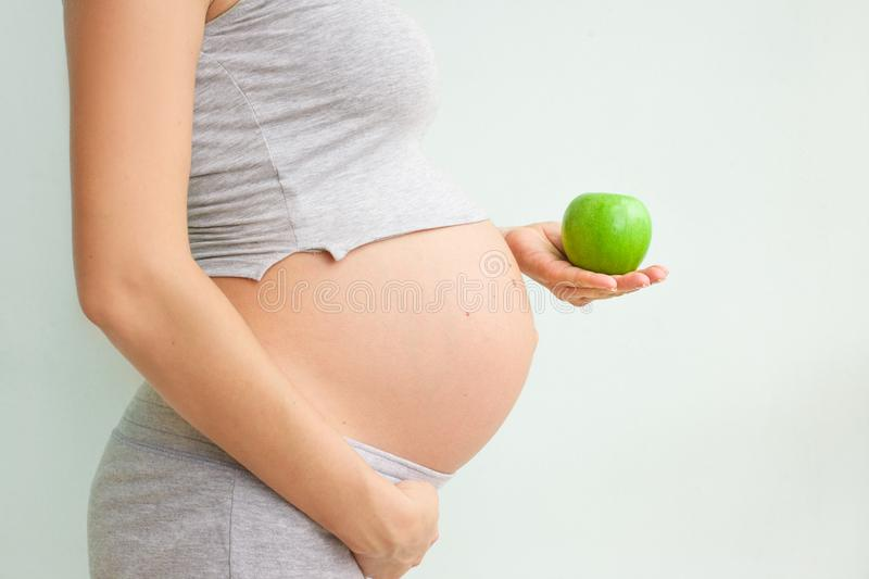 Pregnant girl holding a green apple. nutrition during pregnancy. Vitamins and pregnancy. Source of iron, pregnant anemia. Pregnant girl holding a green apple stock photos