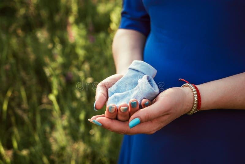 Pregnant girl holding little blue socks royalty free stock photo