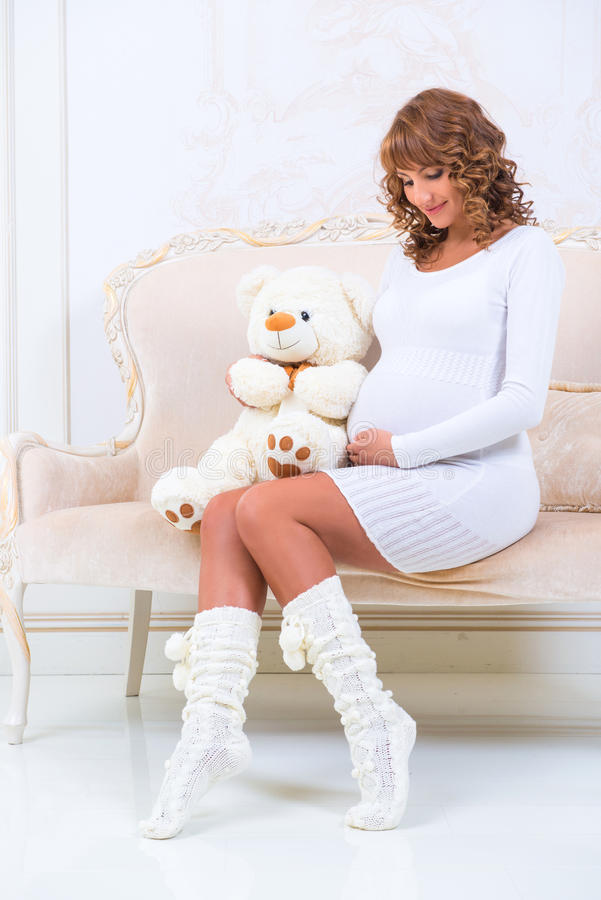Pregnant girl in knitted dress with teddy bear looks at belly.  royalty free stock image