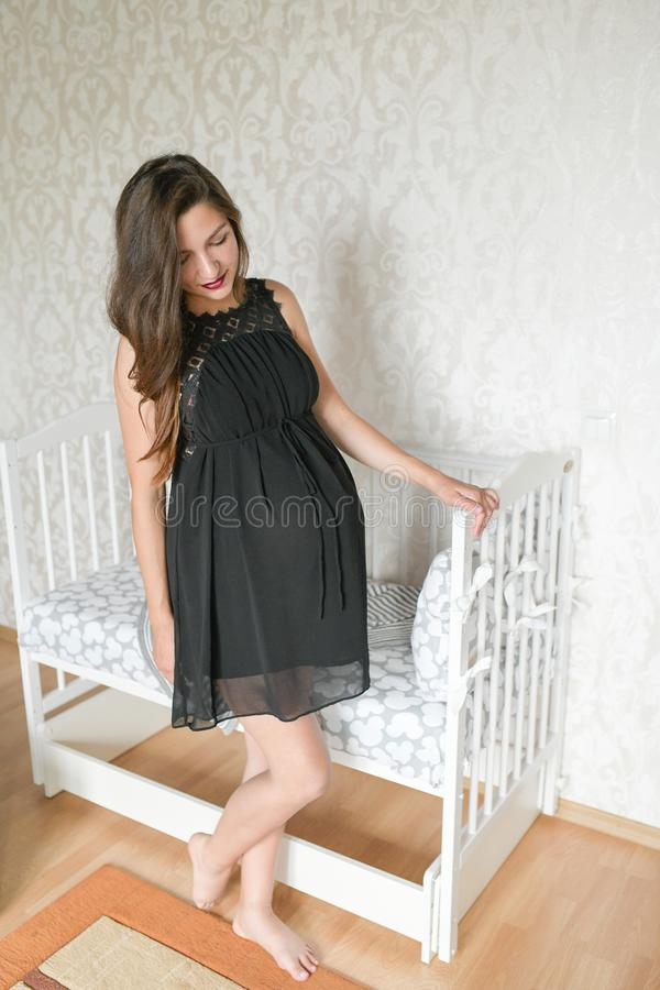 Pregnant girl near the bed for a child. kravatka white color for the child. preparing for the birth of a child. photo of a. Pregnant woman standing near the bed stock photography
