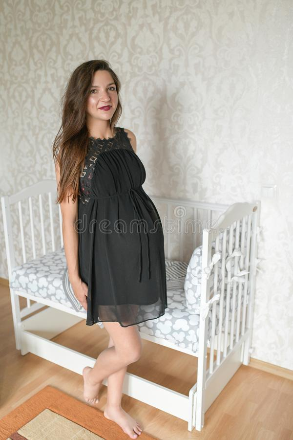 Pregnant girl near the bed for a child. kravatka white color for the child. preparing for the birth of a child. photo of a stock photography
