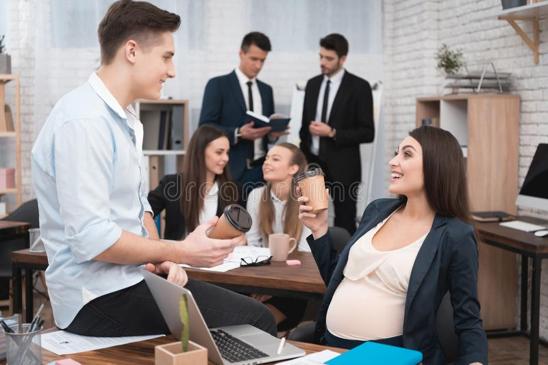 Pregnant girl in office is drinking coffee with colleague in office. Pregnant with colleagues. stock photo