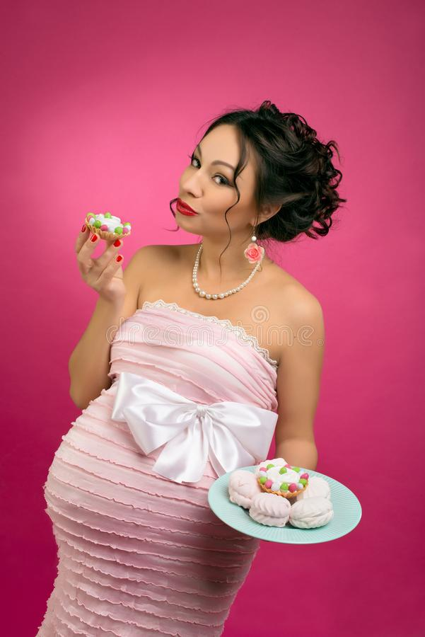 Pregnant girl in pin-up style with a cake in a pink dress on a pink background stock photography