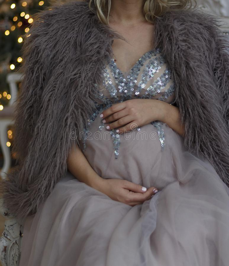 Pregnant girl sits on the couch in a blue dress with sparkles in royalty free stock photography