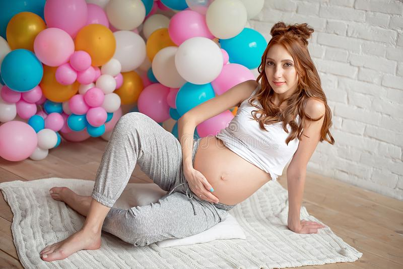 Pregnant girl sits on the floor. stock photography