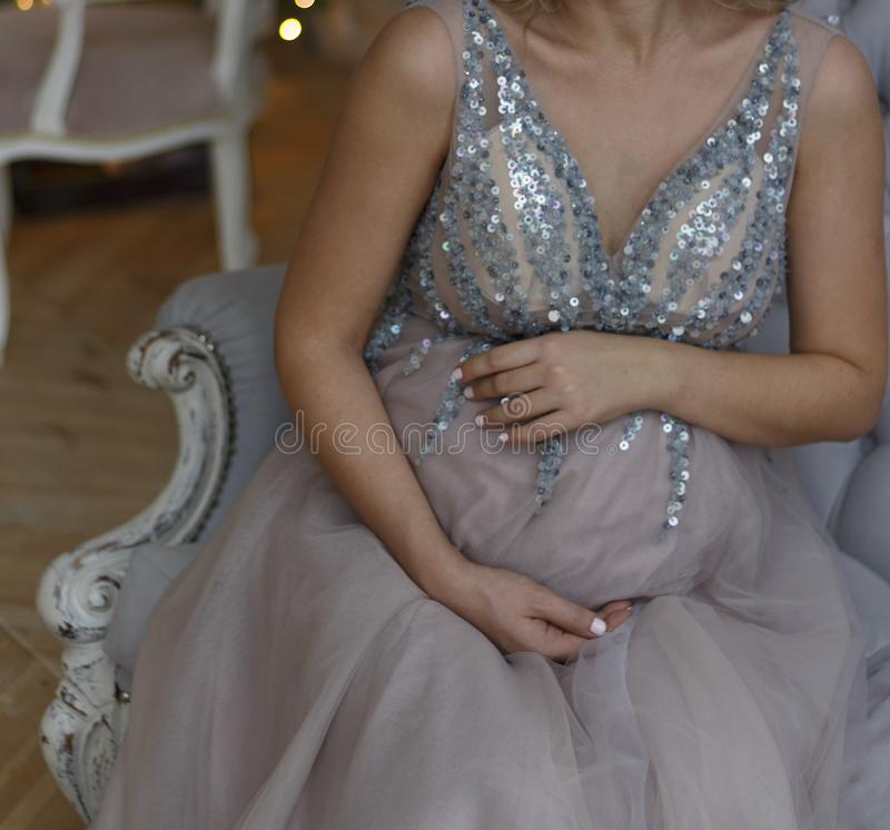 Pregnant girl sits on the couch in a blue dress with sparkles royalty free stock photo