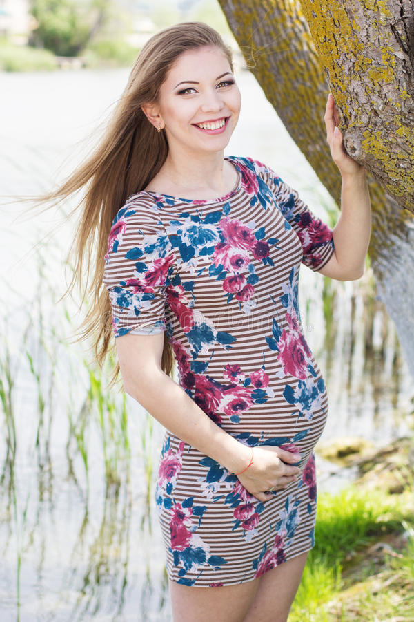 Pregnant girl is standing near river royalty free stock images