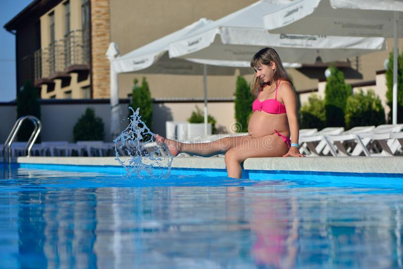 Pregnant girl sunbathing by the pool stock photography
