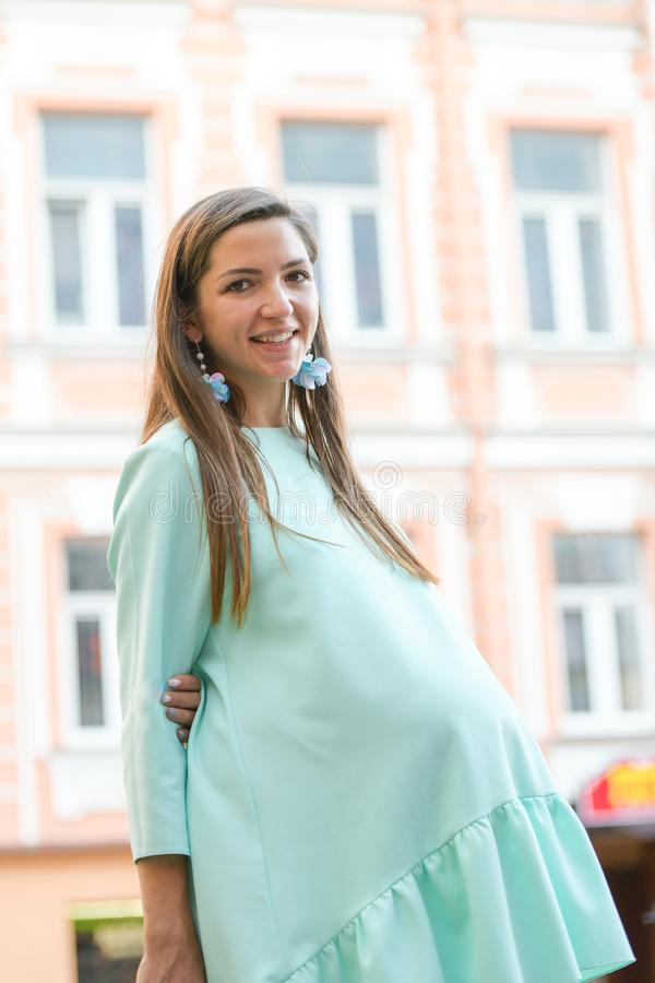 A pregnant girl walks through the city. In a crowded place. listen to street music.  royalty free stock photo