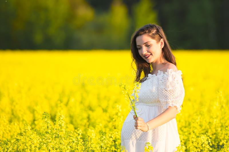 Pregnant girl in a white dress. Outdoor natural portrait of beautiful pregnant woman in white dress stock photography