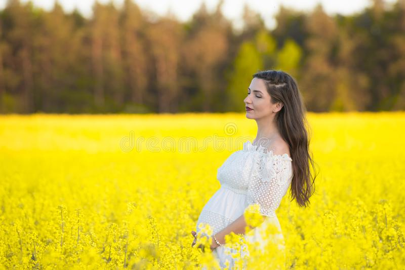Pregnant girl in a white dress. Outdoor natural portrait of beautiful pregnant woman in white dress royalty free stock photo
