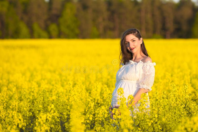 Pregnant girl in a white dress. Outdoor natural portrait of beautiful pregnant woman in white dress stock photos