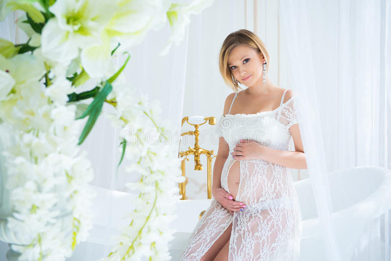 Pregnant girl in a white lace dress sitting in the interior with flowers and hugs belly stock images