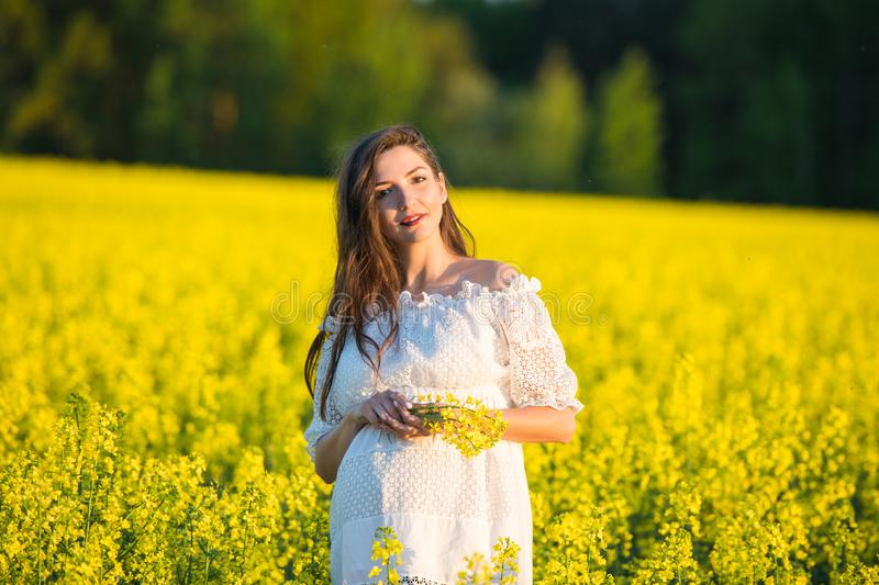 Pregnant girl on a yellow background. looks at his stomach, imagines his unborn child. Maternity concept.  royalty free stock photos