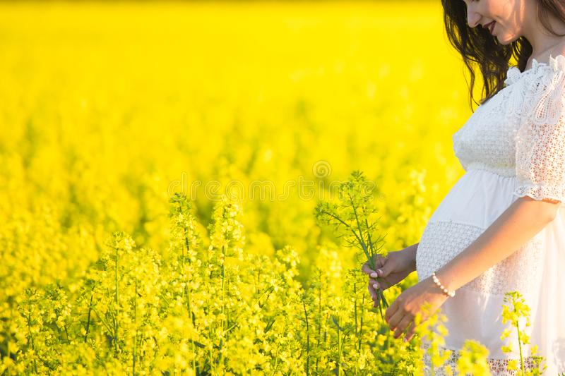 Pregnant girl on a yellow background. looks at his stomach, imagines his unborn child. Maternity concept.  royalty free stock photo