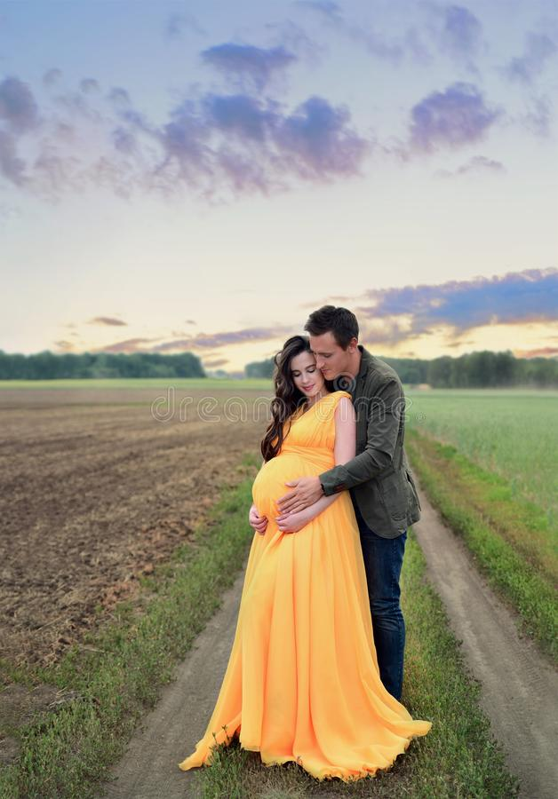 Pregnant girl with a young man hug standing, next to the field at sunset stock images
