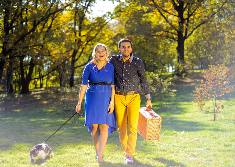 Pregnant happy and smiling couple on picnic with cat royalty free stock photography