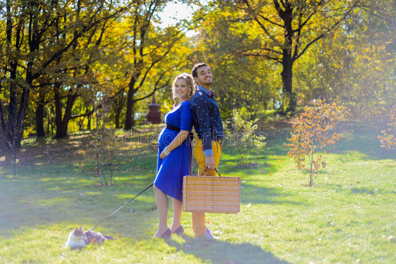 Pregnant happy and smiling couple on picnic with cat stock images