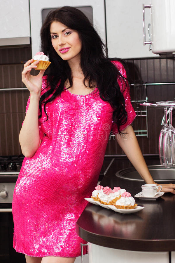 Pregnant happy woman in kitchen eating cakes. Pregnant happy woman is wearing pink dress and staying in kitchen with sweet cakes royalty free stock photography
