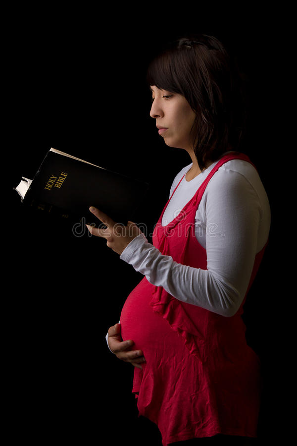 Pregnant Hispanic Woman Reading the Bible royalty free stock image