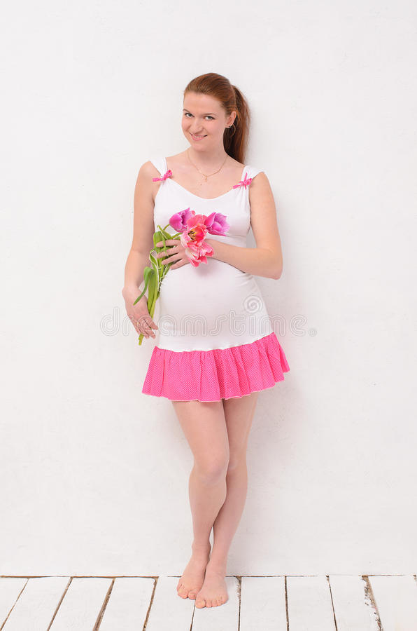 Pregnant holding a bouquet of tulips stock photos