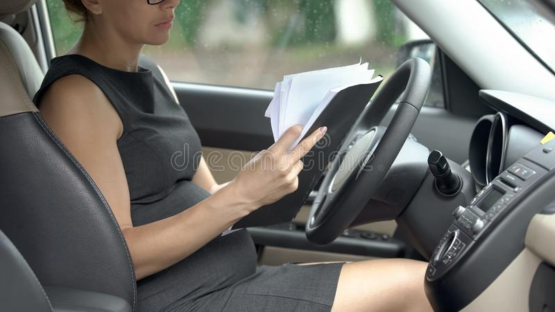 Pregnant lawyer reading documents in auto, working during third trimester. Stock photo royalty free stock photography
