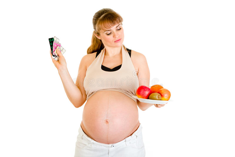 Download Pregnant Making Choice Between Pills And Fruits Stock Image - Image: 18419835