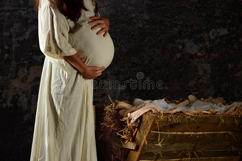 Pregnant Mary in Front of Manger. Pregnant Mary holding stomach in front of Manger royalty free stock photos