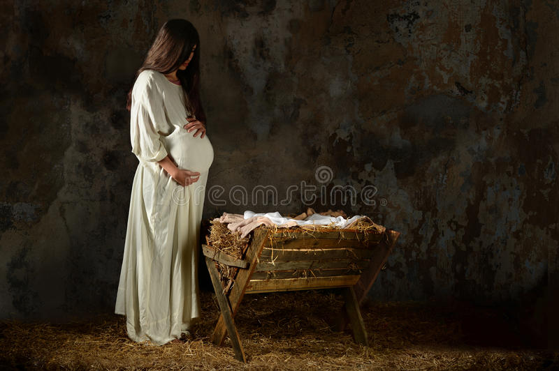 Pregnant Mary Looking at the Manger. Pregnant Mary holding stomach and looking at manger on Christmas Eve royalty free stock images