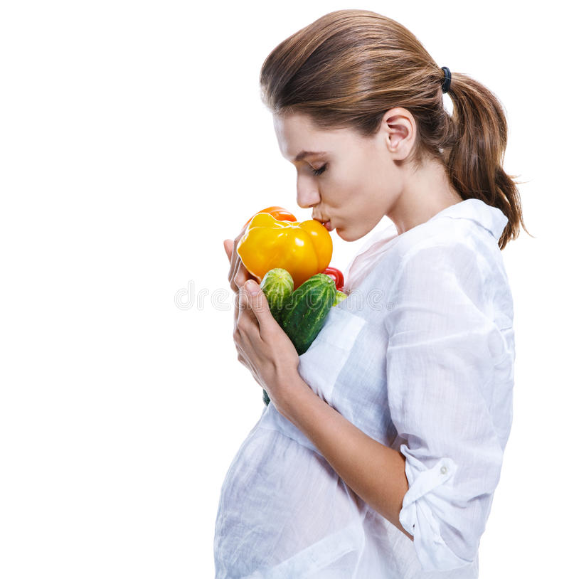 Pregnant moms choose health life - isolated on white background. Parturient girl of the european appearance promotes a healthy lifestyle by eating health food royalty free stock photos