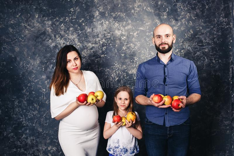 Pregnant mother, bearded father, and little daughter are holding apples in their hands and smiling stock photos