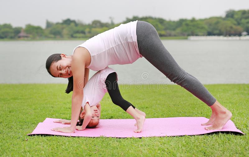 Pregnant mother and her daughter doing yoga in the public park stock photos