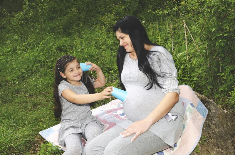 Pregnant mother and her daughter listening her belly stock images