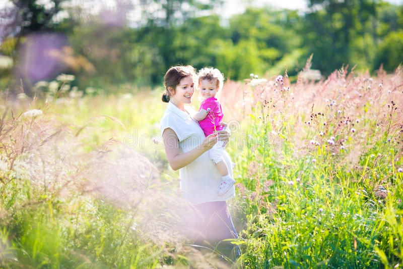 Pregnant mother and her toddler walking in meadow. Pregnant mother and her toddler walking in a sunny meadow on summer day royalty free stock photo