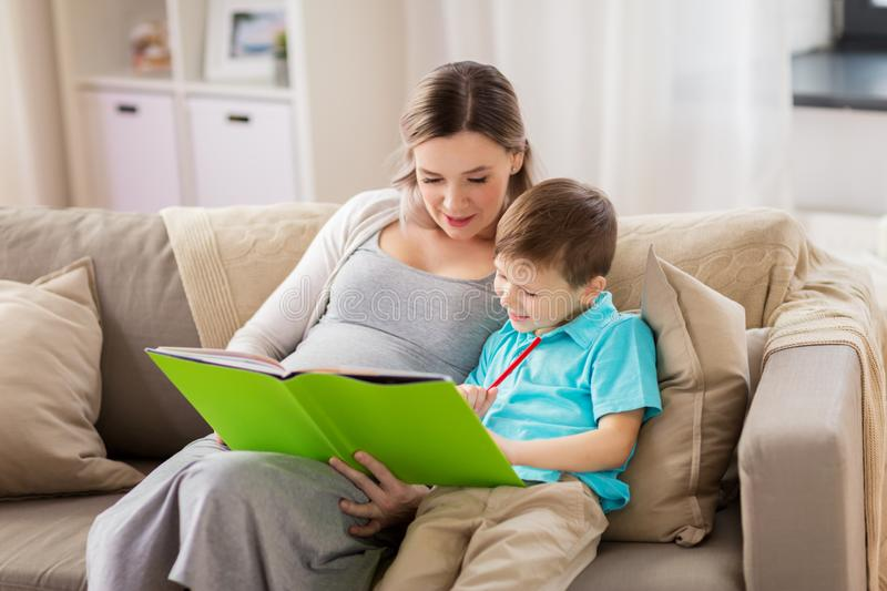 Pregnant mother and little son with book at home royalty free stock images