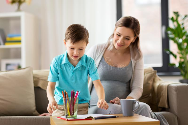 Pregnant mother and son with workbook at home. Family, education and pregnancy concept - happy pregnant mother and little son with workbook writing or drawing at royalty free stock images