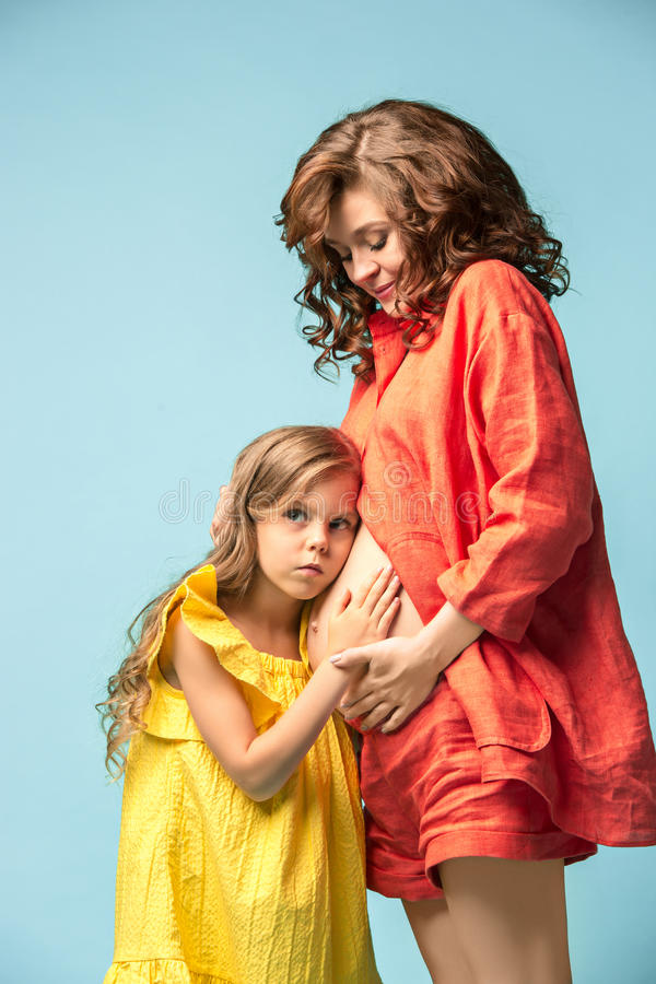 Pregnant mother with teen daughter. Family studio portrait over blue background stock image