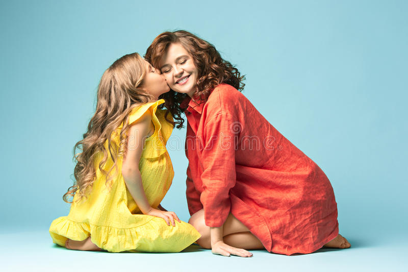 Pregnant mother with teen daughter. Family studio portrait over blue background stock images