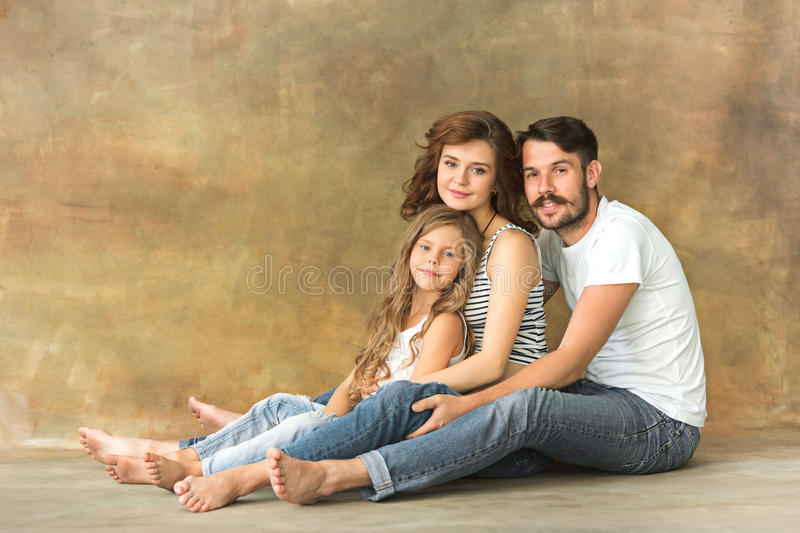 Pregnant mother with teen daughter and husband. Family studio portrait over brown background royalty free stock images