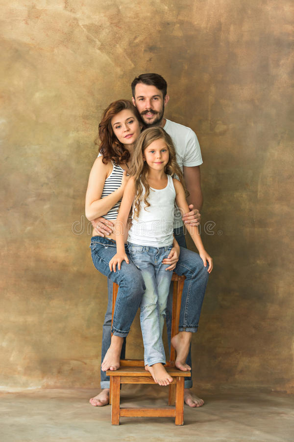 Pregnant mother with teen daughter and husband. Family studio portrait over brown background royalty free stock photos