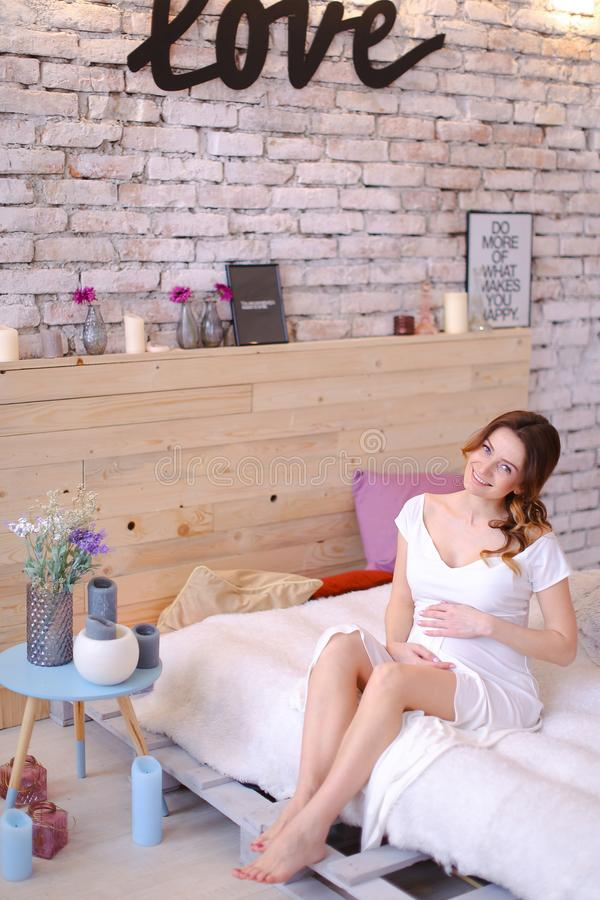 Pregnant nice woman holding belly and sitting on bed in bedroom, inscription love on brick wall. royalty free stock image