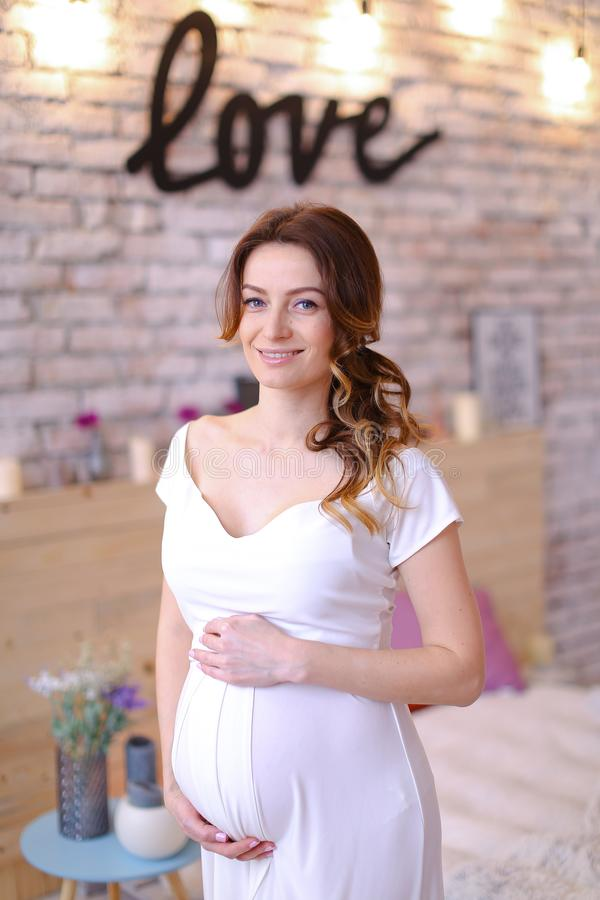 Pregnant nice woman wearing white dress holding beally, inscription love on brick wall. stock photography