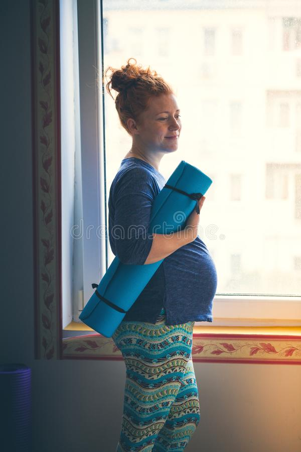 Pregnant red-haired young woman before yoga class. Pregnant smiling red head young woman stand by window with mat prepare for yoga class stock photography